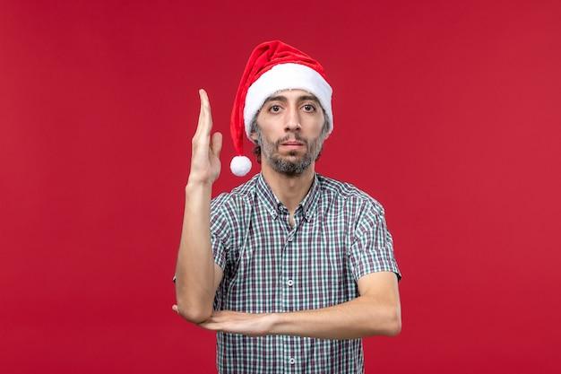 Vue de face jeune homme levant la main sur le mur rouge rouge nouvel an vacances mâle