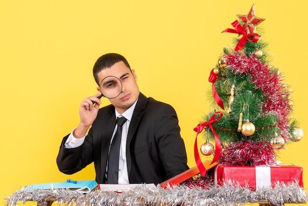 Vue de face jeune homme avec lupa optique dans la main à la recherche d'un œil à travers l'arbre de noël et cadeaux