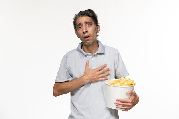 Vue de face jeune homme mangeant des chips de pomme de terre regarder un film sur un bureau blanc