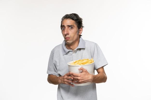 Vue de face jeune homme mangeant des chips de pomme de terre regarder un film sur une surface blanche légère