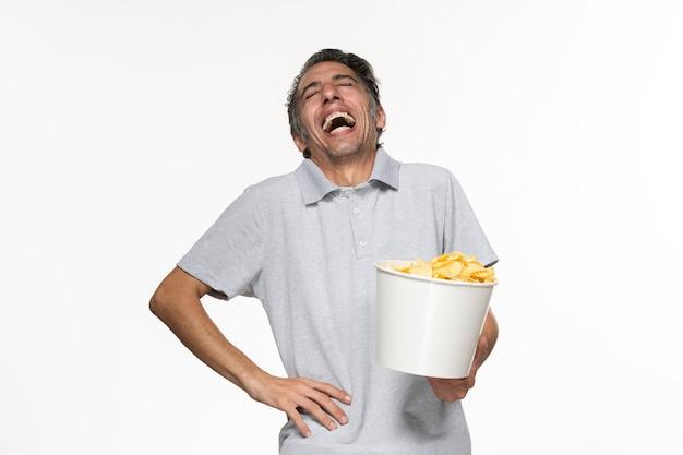Vue de face jeune homme mangeant des chips de pomme de terre en riant sur une surface blanche