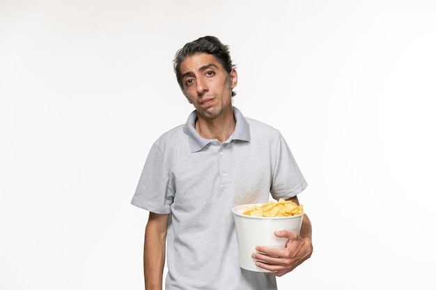 Vue de face jeune homme mangeant des croustilles en regardant un film sur une surface blanche