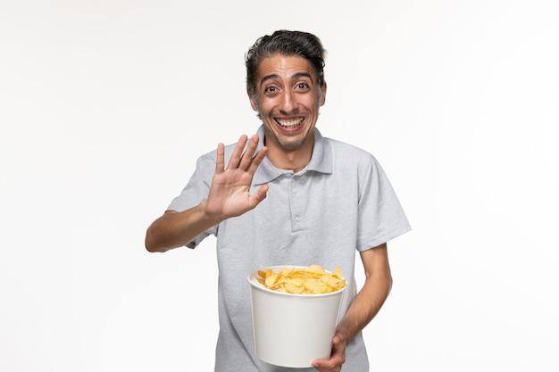 Vue de face jeune homme mangeant des croustilles avec des rires sur une surface blanche