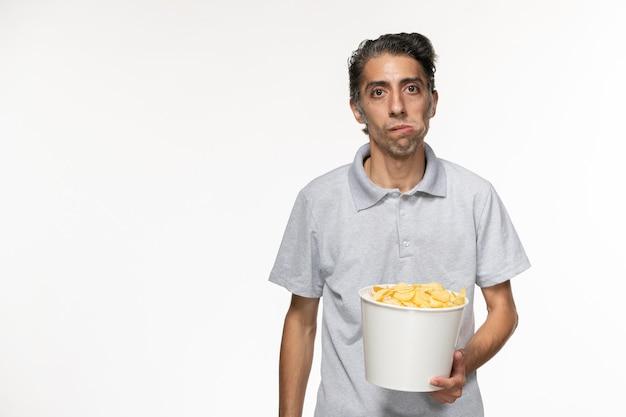 Vue de face jeune homme mangeant des croustilles sur la surface blanche légère