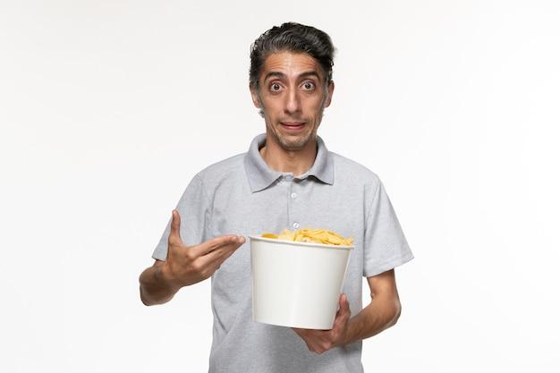 Vue de face jeune homme mangeant des croustilles sur une surface blanche