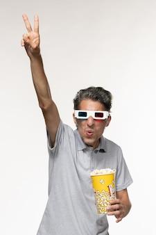 Vue de face jeune homme mangeant du pop-corn dans des lunettes de soleil sur une surface blanche