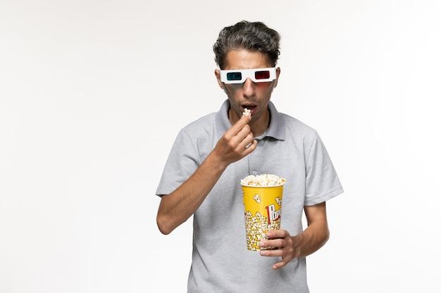Vue De Face Jeune Homme Mangeant Du Pop-corn Dans Des Lunettes De Soleil Sur Une Surface Blanche Photo gratuit