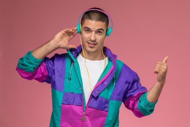 Vue de face jeune homme en manteau coloré, écouter de la musique sur fond rose clair