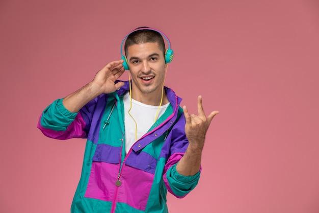 Vue de face jeune homme en manteau coloré, écouter de la musique sur le fond rose