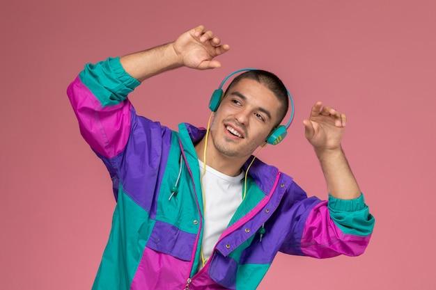 Vue de face jeune homme en manteau coloré, écouter de la musique avec des mouvements de danse sur le fond rose