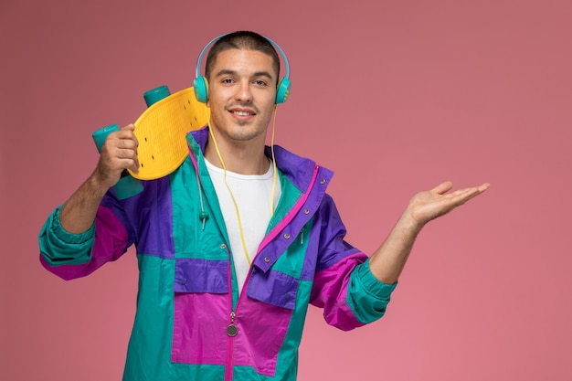 Vue de face jeune homme en manteau coloré, écouter de la musique tenant une planche à roulettes sur le bureau rose mâle