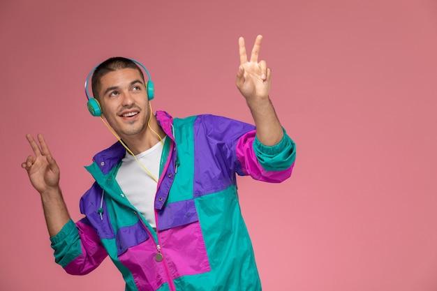Vue de face jeune homme en manteau coloré, écouter de la musique tout en dansant sur le fond rose