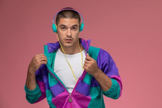 Vue de face jeune homme en manteau coloré posant et écoutant de la musique sur fond rose
