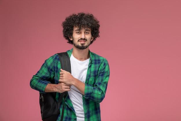 Vue de face jeune homme marchant à l'université avec sac noir