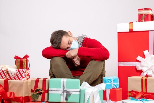 Vue de face jeune homme avec masque dormir autour des cadeaux de noël
