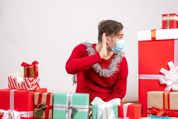 Vue de face jeune homme avec masque écoutant quelque chose assis autour de cadeaux de noël