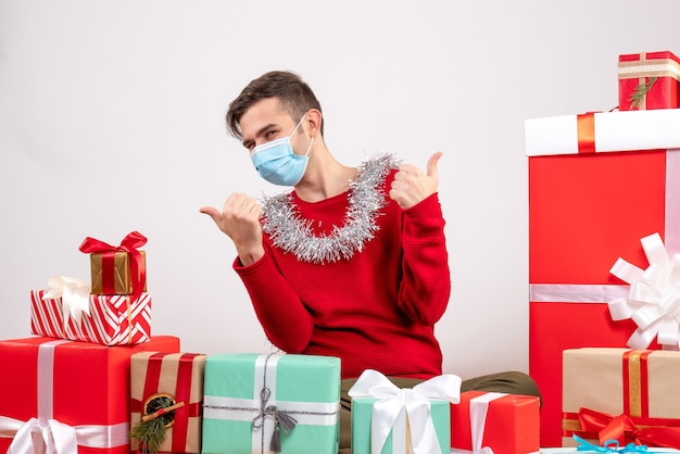 Vue de face jeune homme avec masque faisant le pouce vers le haut signe avec les deux mains assis autour de cadeaux de noël