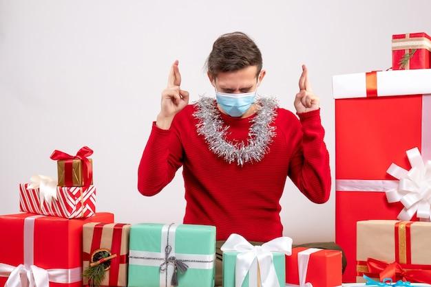 Vue de face jeune homme avec masque faisant signe de bonne chance assis autour de cadeaux de noël