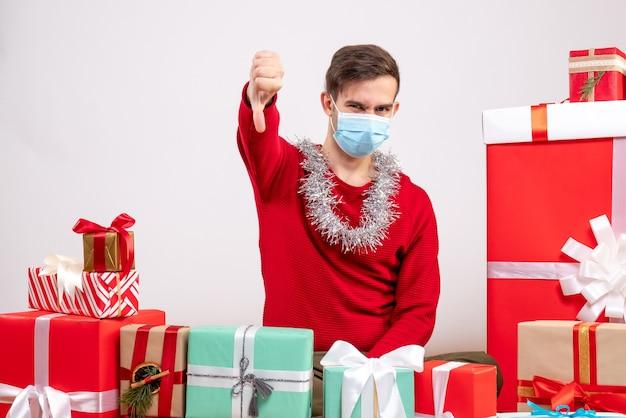 Vue de face jeune homme avec masque faisant signe de pouce vers le bas assis autour de cadeaux de noël