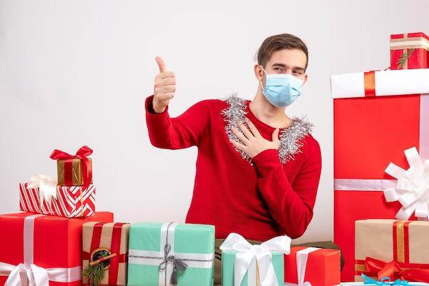 Vue de face jeune homme avec masque médical faisant le pouce vers le haut signe assis autour de cadeaux de noël