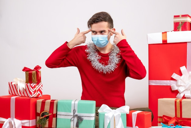 Vue de face jeune homme avec masque mettant les doigts à son temple assis autour de cadeaux de noël