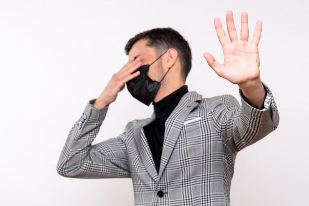 Vue de face jeune homme avec un masque noir couvrant ses yeux debout sur fond blanc isolé