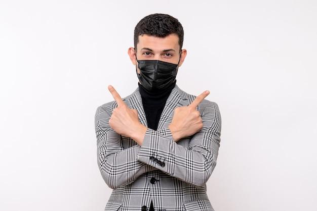 Vue de face jeune homme avec masque noir croisant les mains debout sur fond blanc isolé