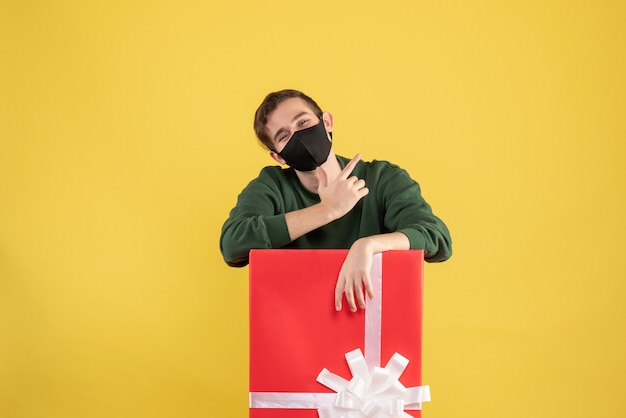 Vue de face jeune homme avec masque noir debout derrière un grand coffret sur jaune