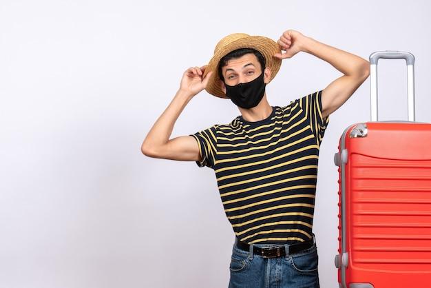 Vue de face jeune homme avec masque noir debout près de valise rouge tenant son chapeau