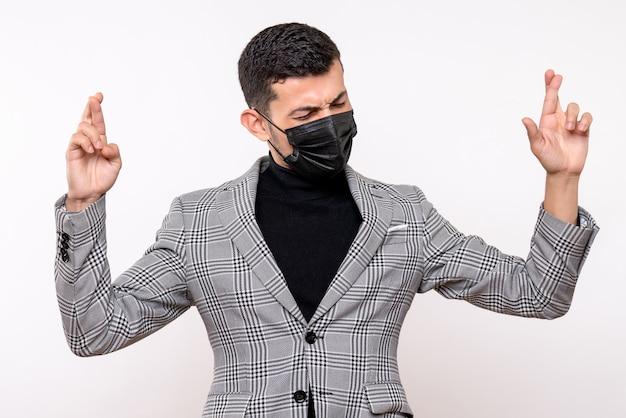 Vue de face jeune homme avec masque noir faisant signe de bonne chance debout sur fond blanc isolé
