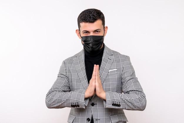 Vue de face jeune homme avec masque noir joignant les mains ensemble debout sur fond blanc isolé