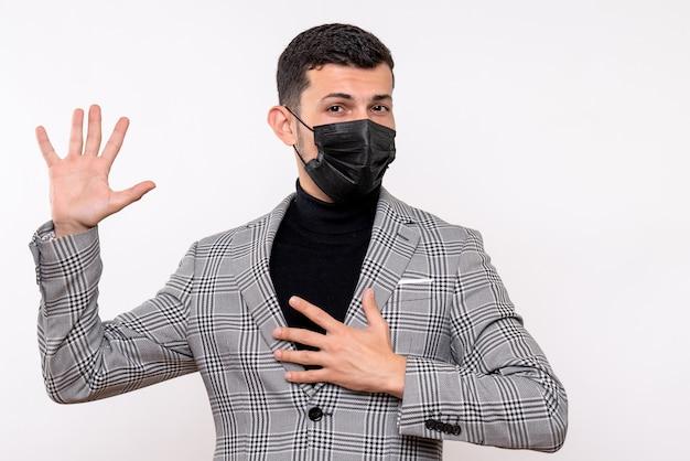Vue de face jeune homme avec masque noir prometteur debout sur fond blanc isolé