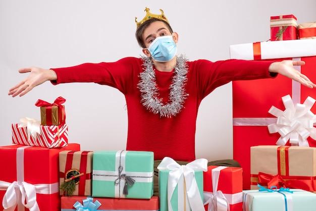 Vue de face jeune homme avec masque ouvrant ses mains assis sur des cadeaux de noël au sol