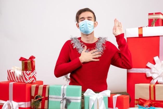 Vue de face jeune homme avec masque prometteur assis autour de cadeaux de noël