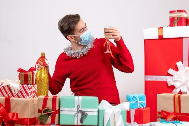 Vue de face jeune homme avec masque regardant champagne assis autour de cadeaux de noël