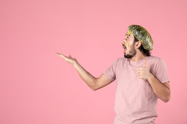 Vue de face jeune homme avec masque sur son visage sur fond rose