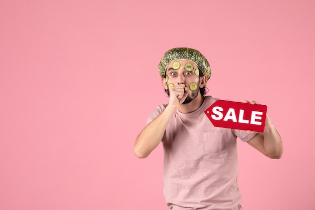 Vue de face jeune homme avec masque sur son visage tenant la plaque signalétique de vente sur fond rose