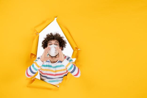 Vue de face jeune homme en masque stérile disant quelque chose sur la couleur jaune covid- photo du virus de la pandémie humaine de santé