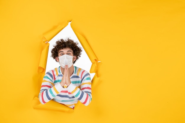 Vue de face jeune homme en masque stérile sur photo couleur jaune santé virus pandémique humain