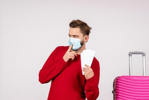 Vue de face jeune homme en masque stérile tenant des billets sur un mur blanc covid avion vacances émotion virus vol voyage couleurs