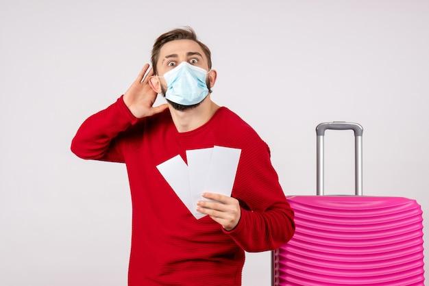 Vue de face jeune homme en masque stérile tenant des billets sur mur blanc voyage covid- vol voyage vacances couleur émotion virus