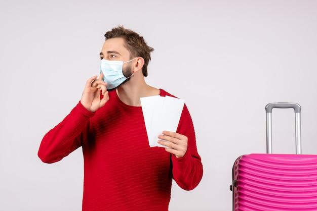 Vue de face jeune homme en masque stérile tenant des billets sur mur blanc voyage covid- voyage vacances couleurs émotion virus vol