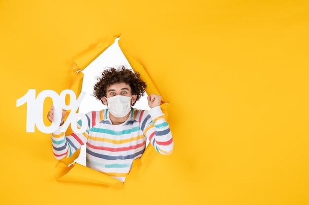 Vue de face jeune homme en masque stérile tenant l'écriture sur photo jaune santé covid coronavirus vente couleur