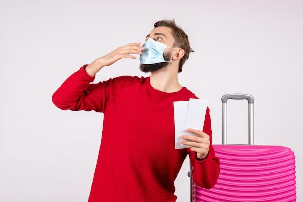 Vue de face jeune homme en masque tenant des billets sur mur blanc voyage covid- vol voyage vacances virus couleur émotion