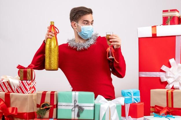 Vue de face jeune homme avec masque tenant du champagne autour de cadeaux de noël