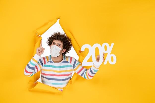 Vue de face jeune homme en masque tenant l'écriture sur la vente jaune coronavirus pandémie santé covid- photo couleur