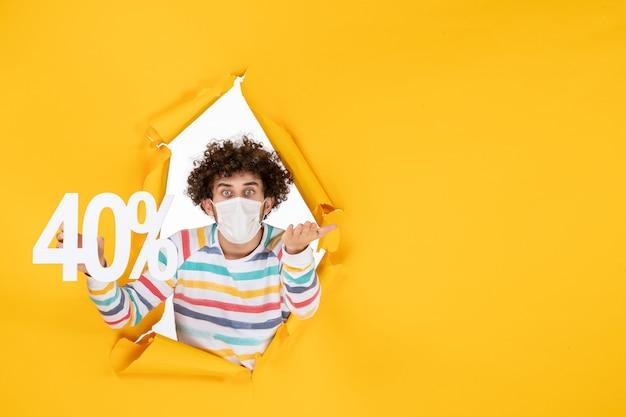 Vue de face jeune homme en masque tenant l'écriture sur le virus jaune pandémie shopping santé covid photo vente couleur