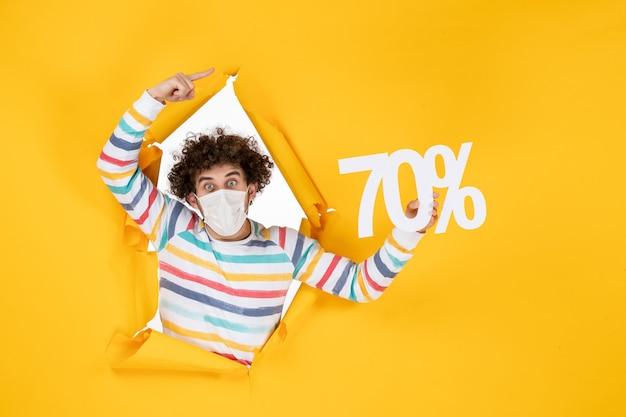 Vue de face jeune homme en masque tenant l'écriture sur le virus de la vente jaune covid- photos shopping