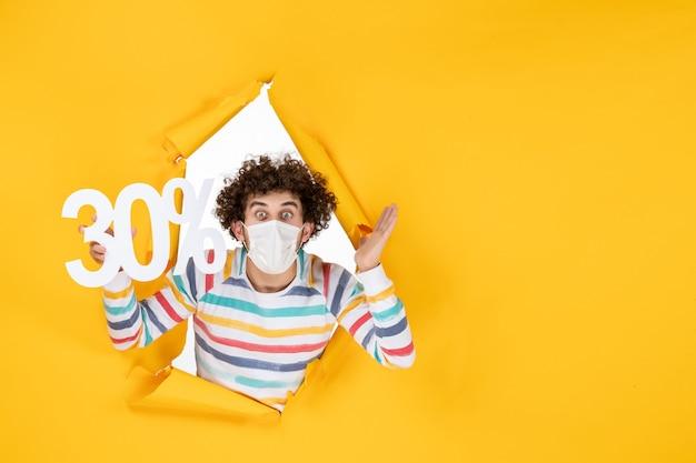 Vue de face jeune homme en masque tenant sur la vente de virus pandémique de photo de santé covid de couleur jaune