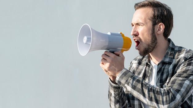 Vue de face jeune homme avec mégaphone